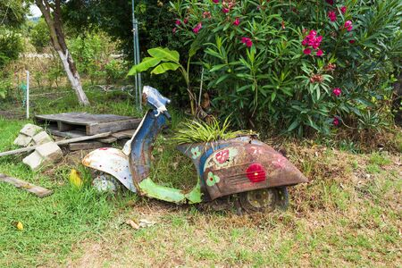 An old abandoned painted motorcycle in a garden at Corfu island