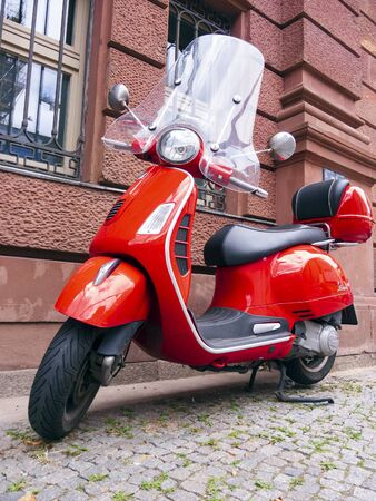 Berlin, Germany - August 13, 2019: A red Vespa stands on the edge of the road in Berlin Editorial