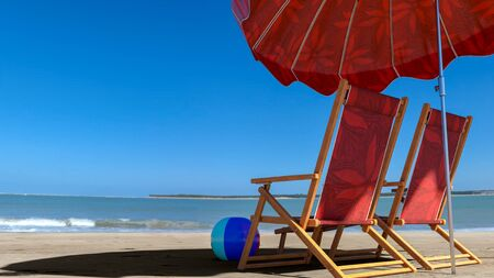 Two empty chairs on beach under opened umbrella with view on sea - 3d rendering 免版税图像