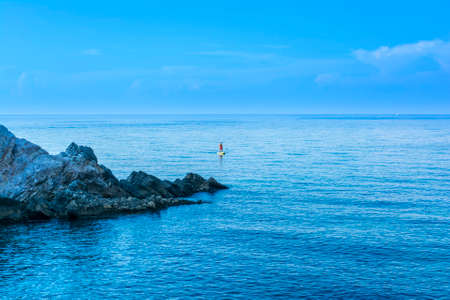 Young man paddling on sup board on calm sea water at Limnionas beach, Greece. 免版税图像