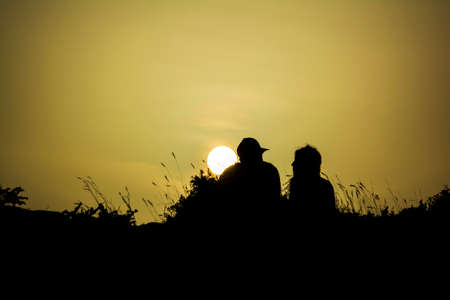 Couple silhouette watching the sun at sunset at Sounion