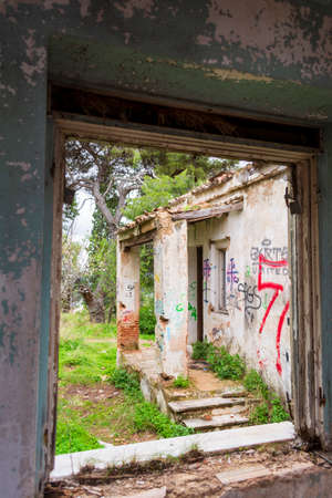 Window view of an abandoned old villa at Pallini, Greece