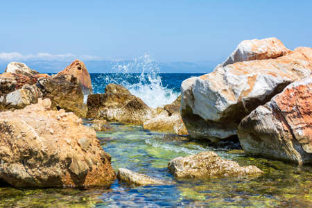 The waves breaking on a stony beach, forming a spray. Greece.