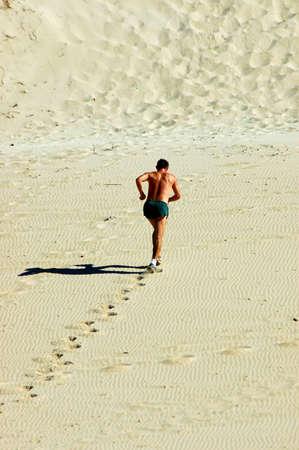 Een gezonde blanke sportieve man rende de duinen in de woestijn Stockfoto