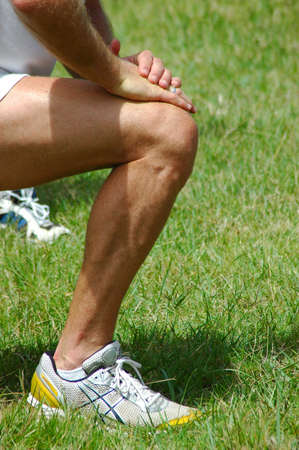 Leg of an athlete with hands on knee stretching after excercising outdoors in nature Standard-Bild