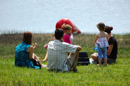 A happy family having a picnic by the lake in summertime
