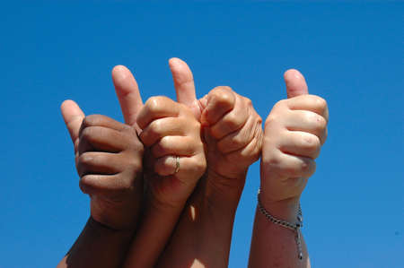 Four female hands as a team: black hand of African American lady and white hands of caucasian women holding up thumbs symbolizing an optimistic and positive future together