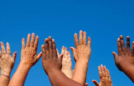 African black and caucasian white hands of four ladies reaching out to the sky symbolizing world freedom for women and new hope