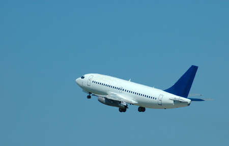 A big blue and white airplane taking off in the air