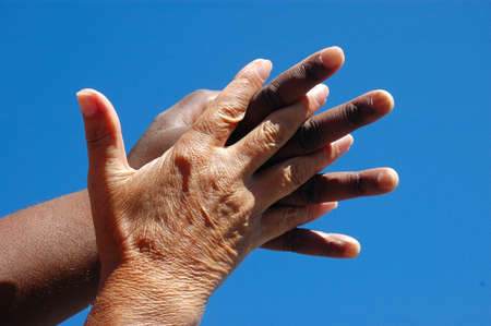 An old caucasian white hand and a young African American black hand holding each other in front of blue sky background