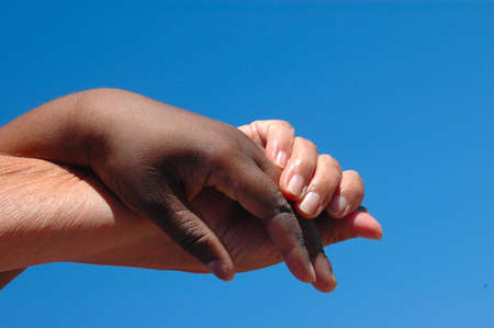 An old caucasian white hand and a young African American black hand holding and helping each other in front of blue sky background Stock Photo