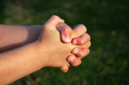 The praying white hands of a happy little caucasian child