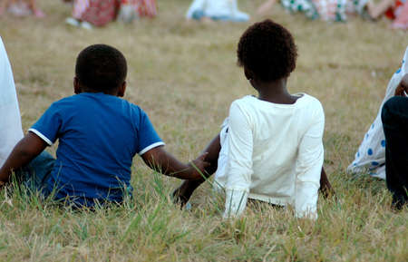 A group of black African children sitting on the grass and watching a soccer game together outdoors in South Africa