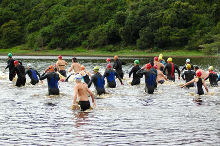 Men and women triathletes jumping into the water for swimming