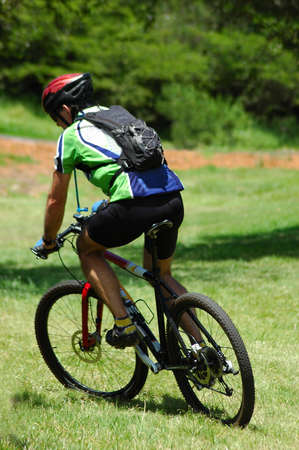 An active caucasian white male mountain biker riding his bicycle in nature