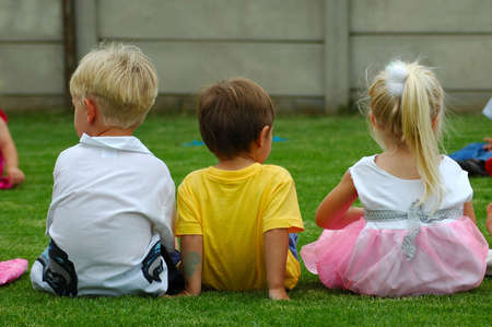 Three caucasian white children: two boy toddlers and a girl child sitting on the lawn in the garden watching other kids playing