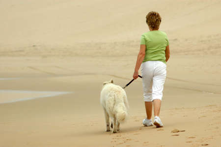 A blond caucasian woman walking her white American Canadian Shepherd dog on the beach on a misty morning