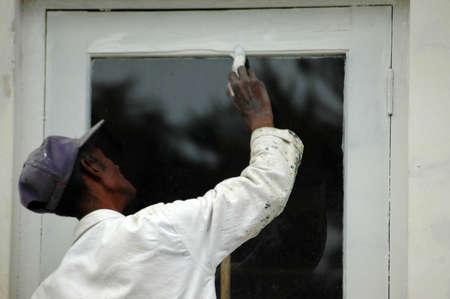 An African American black man at work painting a white door  Standard-Bild