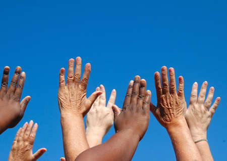 African black and caucasian white hands of four ladies reaching out to the sky symbolizing world freedom for women