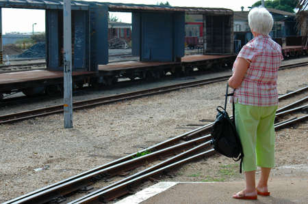 An elderly matured senior white caucasian woman waiting for the train at the railway station outside  Stock Photo