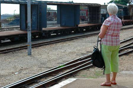An elderly matured senior white caucasian woman waiting for the train at the railway station outside  Standard-Bild