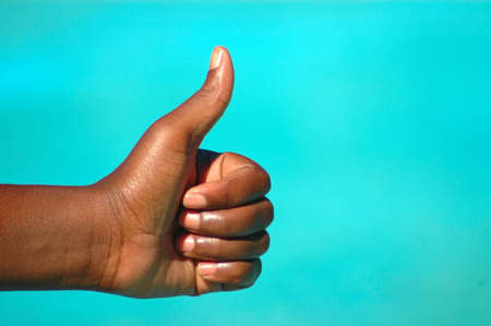 A black hand of an African American woman with thumb up to show a positive future