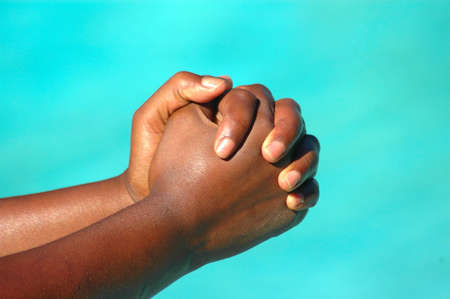 An African American woman holding her black hands together praying to God outdoors  Standard-Bild