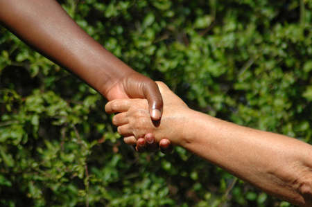 Handshake between a black hand of an African American woman and a white hand of an caucasian woman holding each other to show there agreement