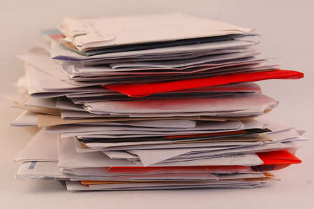 A bulk of colorful letters and junk mail on a table isolated on white background
