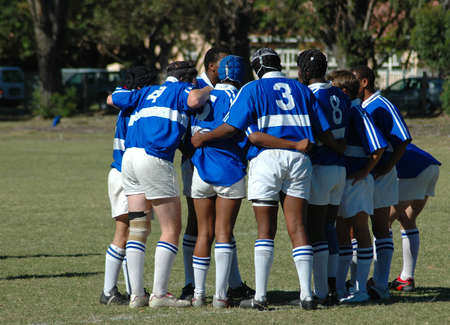 A male Rugby team with caucasian and African American players in blue and white jerseys standing together and showing team spirit in a game on the field outdoors
