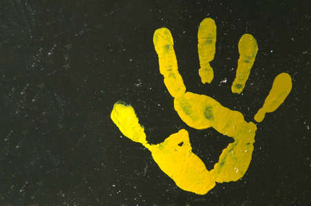A yellow painted open hand print with five fingers on a black background of an old garbage drum  Stock Photo
