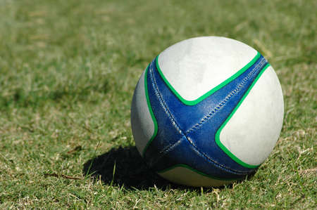 A blue, green and white rugby ball on the lawn in the grass of the field Stock Photo