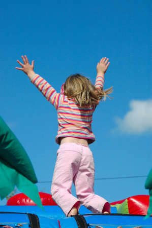 Rear view of a white caucasian girl child with long blond hair raising up her little hands in the air having great fun by jumping on a jumping castle on the playground outdoors in sunshine  Stock Photo