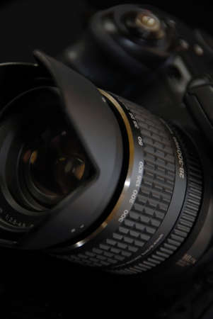 the lens to modern profesionalny camera SLR on the black background