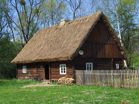 Old wooden hut in village, green grass around