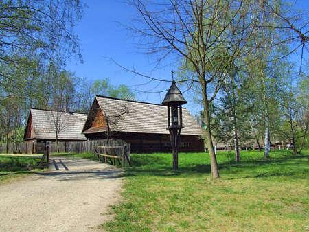 Old wooden hut in village, green grass around photo