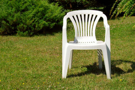 White plastic chair on the grass in the garden Stock Photo
