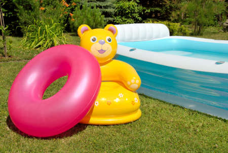 Inflatable armchair and tire near the pool Stock Photo