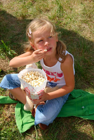 Young girl siting on the grass and eats popcorn.