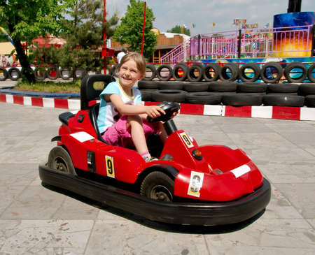 Smiling girl is driving bumper car