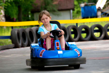 car race track: Girl is driving bumper car Stock Photo