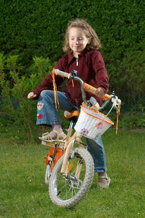 A young girl on a bicycle. photo