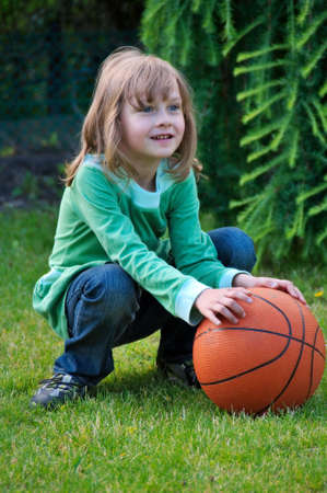 Small young girl hold on to the ball Stock Photo - 5090098