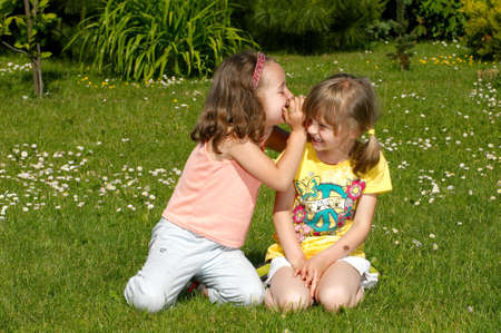 Two girls whispering secrets to each other photo