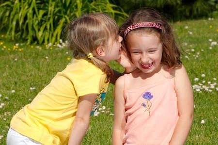 ciascuno: Due ragazze sussurrando segreti gli uni agli altri Archivio Fotografico
