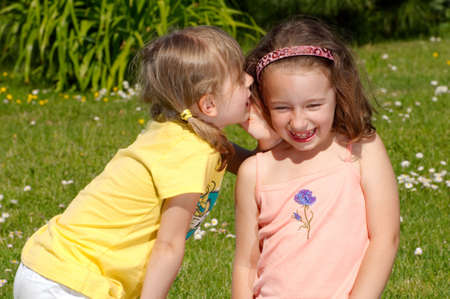 Two girls whispering secrets to each other Stock Photo