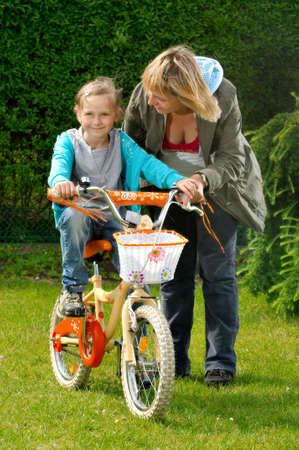 helps: Mother helps daughter to ride on the bike