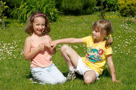 girl bonding: Two girls sitting in the garden