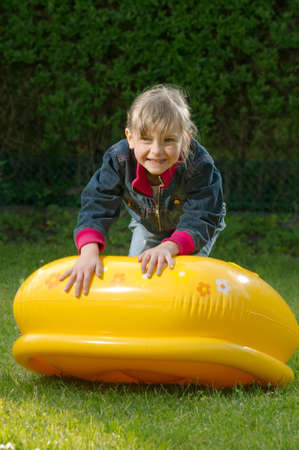 young girl is climbing on the blowed toy Stock Photo