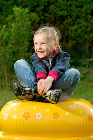 young girl is sitting on the blown toy